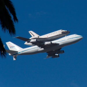 space shuttle on top of a plane