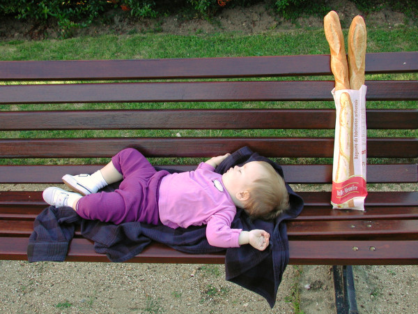 Child sleeping on a park bench